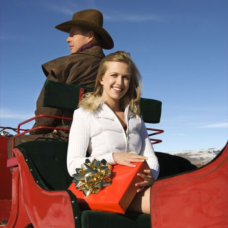 Young adult Caucasian woman holding present and mid-adult man in sleigh. photo