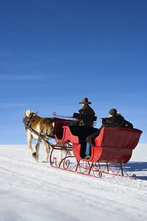 Mid adult man driving horse drawn sleigh with young couple in back. photo