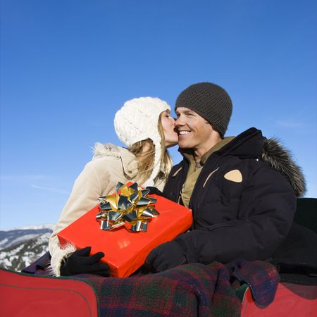 Young Caucasian yoman kissing cheek of man in a sleigh in winter. photo