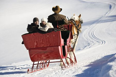 couple winter: Rear view of man driving horse drawn sleigh with young couple looking back at viewer.