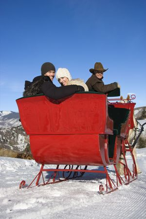 horse sleigh: Rear view of young Caucasian couple and mid-adult man looking over shoulder at viewer from horse drawn sleigh. Stock Photo