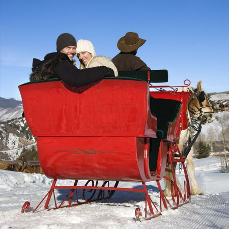 horse sleigh: Rear view of man driving horse drawn sleigh with young couple looking back at viewer.