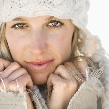 Young adult Caucasian woman in winter attire holding hands to face looking at viewer. photo