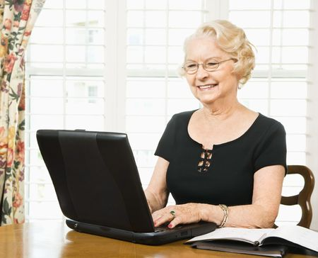 70s adult: Mature Caucasian woman using laptop in living room. Stock Photo
