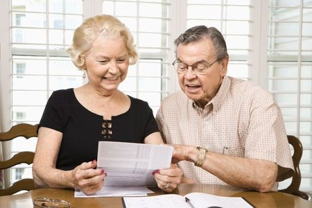 70s adult: Mature Caucasian couple looking at their bills. Stock Photo