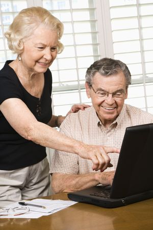 70s adult: Mature Caucasian couple looking at laptop. Stock Photo