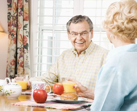 70s adult: Mature Caucasian couple having breakfast together.