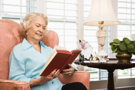 Mature Caucasian woman sitting in chair reading a book. photo