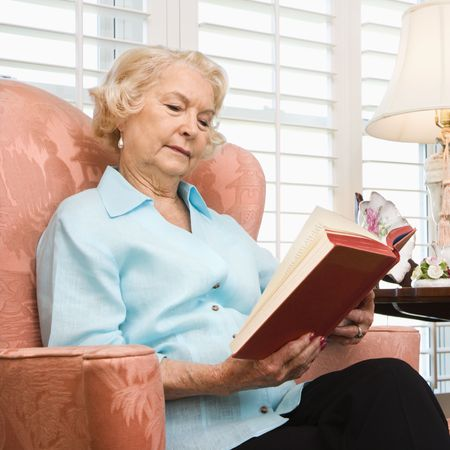 70s adult: Mature Caucasian woman sitting in chair reading a book.