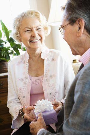 70s adult: Mature Caucasian man giving present to mature Caucasian woman.