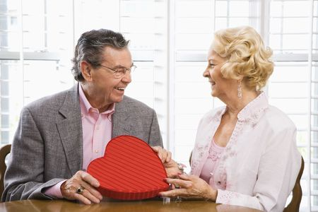 Mature Caucasian man giving Valentine heart box to mature Caucasian woman. photo