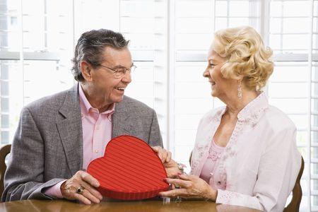 Mature Caucasian man giving Valentine heart box to mature Caucasian woman. photo