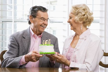 male senior adult: Mature Caucasian couple holding birthday cake looking at each other.