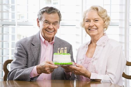 70s adult: Mature Caucasian couple holding birthday cake looking at viewer.