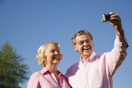 70s adult: Mature Caucasian couple taking picture of themselves.