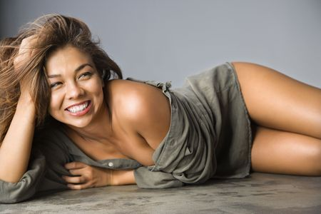 Attractive Asian female lying on ground with happy expression.