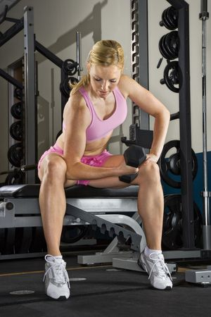 Caucasian mid-adult woman lifting weights in gym.