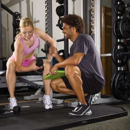 Caucasian mid-adult woman lifting weights while African-American male trainer watches. photo