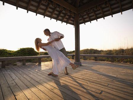 Caucasian couple dancing under gazebo at the beach.