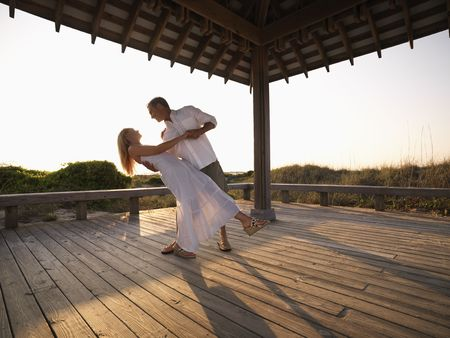 Caucasian couple dancing under gazebo at the beach. photo