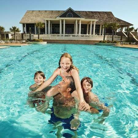 Caucasian family at pool with clubhouse in background. Stock Photo