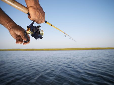sports fishing: African-American male hand holding fishing rod and reeling the other hand.
