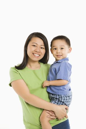 half length posed: Asian mother holding son on hip smiling in front of white background.