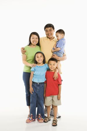 Asian parents with three children standing in front of white background.