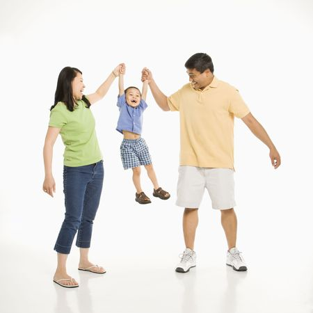 Asian mother and father holding hands with son and lifting him up in front of white background.