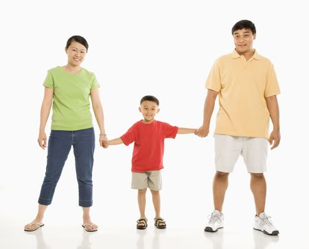Asian parents holding hands with son in front of white background. Stock Photo - 1868854