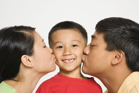 filipino people: Asian mother and father kissing opposite cheeks of smiling son in front of white background.
