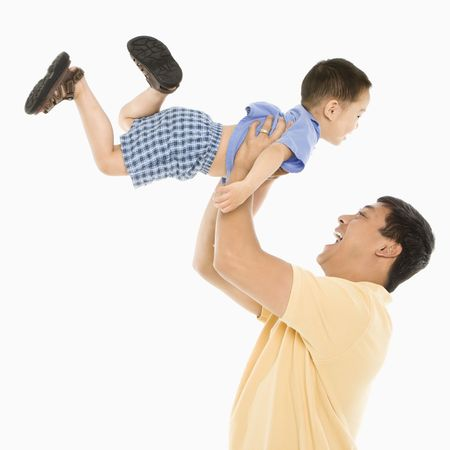 Asian father lifting son up into air in front of white background. photo