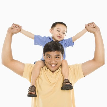 half length posed: Asian father holding son on shoulders smiling in front of white background.