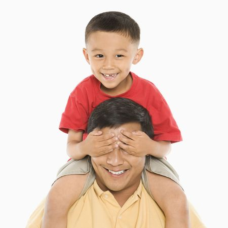 Asian boy sitting on fathers shoulders with hands over his eyes in front of white background. photo