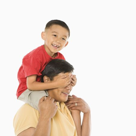 half length posed: Asian boy sitting on fathers shoulders with hands over his eyes in front of white background.