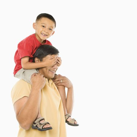 Asian boy sitting on fathers shoulders with hands over his eyes in front of white background.
