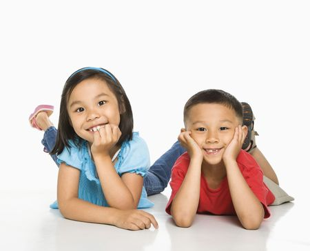 filipino: Young Asian brother and sister lying on floor with head on hands.
