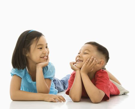 eachother: Young Asian brother and sister lying on floor with head on hands looking at eachother smiling. Stock Photo