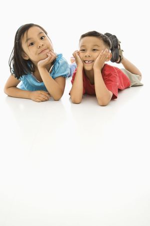 Asian brother and sister lying on floor with heads on hands. Stock Photo - 1868870
