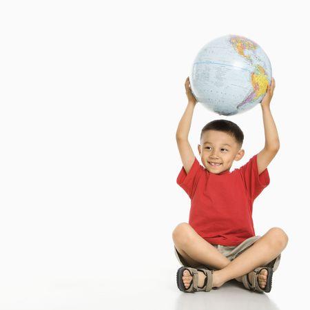 Asian boy sitting on floor holding Earth globe over his head. Stock Photo - 1868852