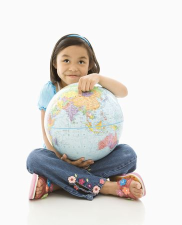 Asian girl sitting on floor holding Earth globe in her lap. Stock Photo - 1868972