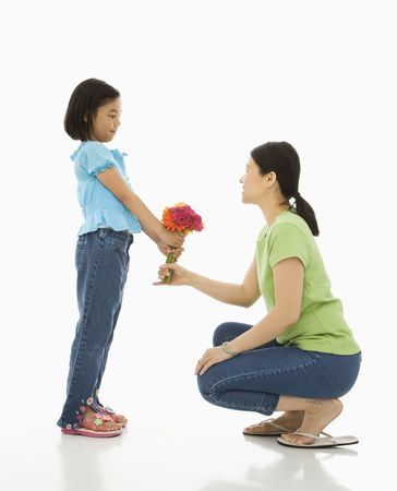 Asian girl handing bouquet of flowers to her mother. Stock Photo - 1868898