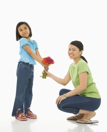 Asian girl handing bouquet of flowers to her mother. photo