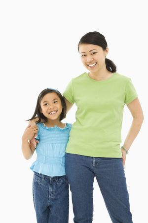 eachother: Asian mother and daughter standing with arms around eachother.