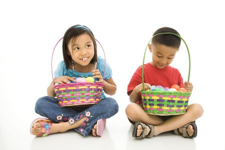 Asian girl and boy sitting on floor holding Easter baskets full of eggs. Stock Photo - 1868983