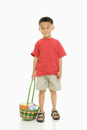 Asian boy standing against white background holding Easter basket. Stock Photo - 1868834