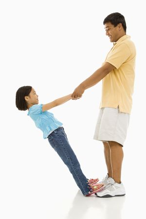 Asian daughter standing on fathers feet holding his hands and leaning back. Stock Photo