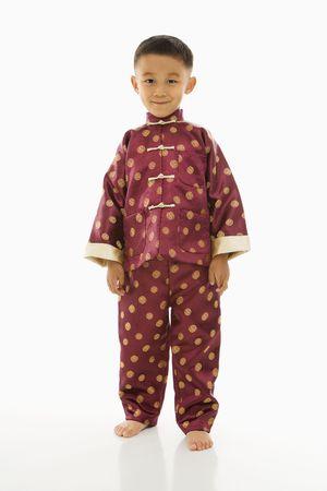 ni�o parado: Asia muchacho de pie contra el fondo blanco en la vestimenta tradicional.