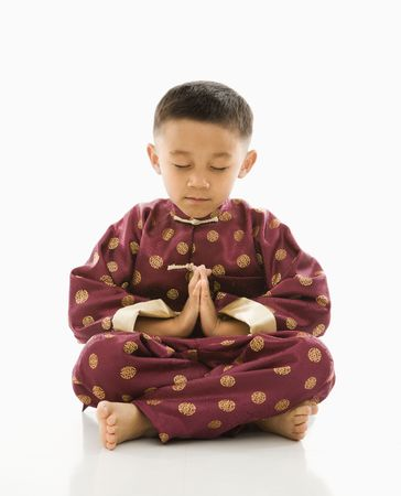 Asian boy sitting meditating against white background in traditional  attire. Stock Photo - 1868945