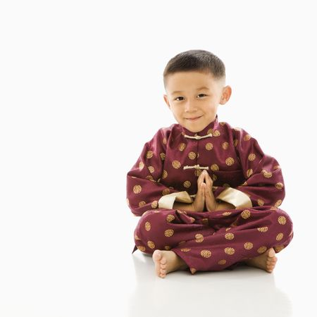 Asian boy sitting meditating against white background in traditional  attire. Stock Photo - 1868872
